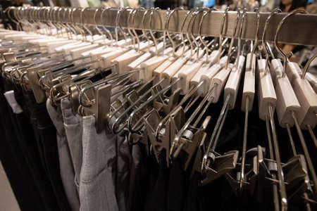A row of hangers with pants and skirts in the store. Sales and shopping concept