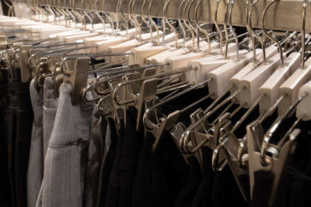 A row of hangers with pants in the store. Sales and shopping concept