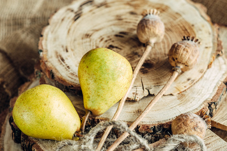 old desk: juicy pears on a wooden background and a sack in a low key