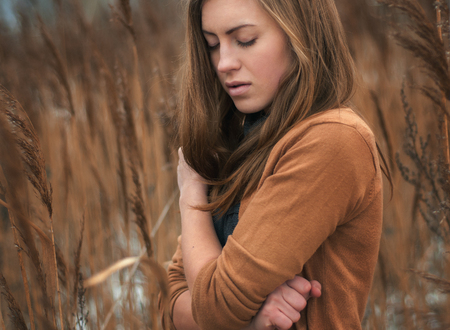big shirt: the girl is freezing in the thick thickets of marsh grass which has dried and has a yellow color