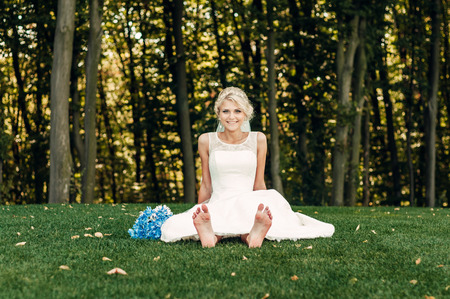 a barefooted young fair-haired bride sits on the grass in an exotic park, in a long white dress with a bouquet of flowers in her hands, a walk after the wedding ceremony, a wedding ceremony
