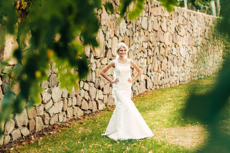 a young fair-haired bride stands on the grass in an exotic park near the stone wall, in a long white dress, a walk after the wedding ceremony, hands on waist