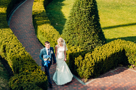 barefooted young fair-haired bride and her fiance walking along the grass in an exotic park, in a long white dress, a walk after the wedding ceremony Stock Photo