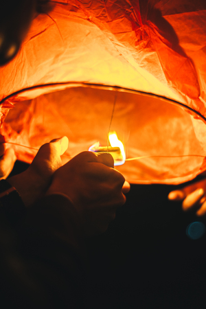 sets fire to a heavenly paper lantern before launching into the dark evening sky, creating a romantic atmosphere