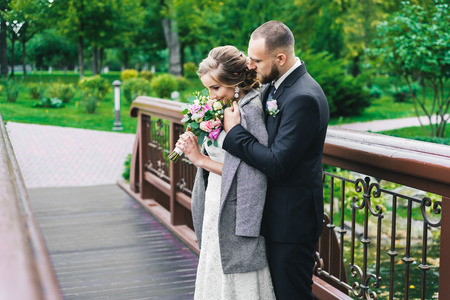 woman in a long white dress with a wedding bouquet along with a bearded bridegroom after a wedding ceremony on a walk in an exotic autumn park.