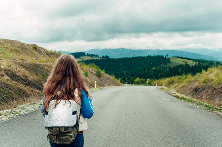 mountain landscape in the autumn fog. girl with a backpack stands with her back and looks at the road Stock Photo