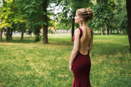 girl, woman in a long waist-fitting festive evening dress with bare back stands in a green park, garden, with a beautiful hairdo