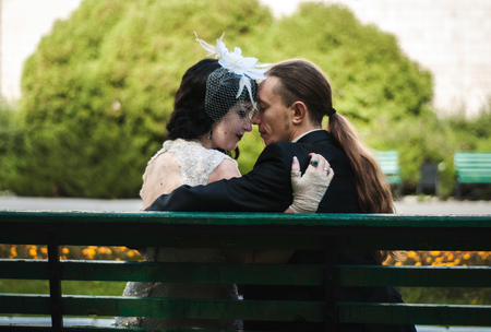 black-haired bride, wife and her fiance, husband on a walk in a green autumn park. she is in a long retro dress with a bouquet, the face in the piercing is hidden under a veil