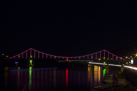 Parkovyi Bridge, which is illuminated with lights in the evening in Kiev with a road and cars near it Stock Photo