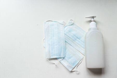 Sanitizer gel or antibacterial soap and face mask for coronavirus preventive measure, top view