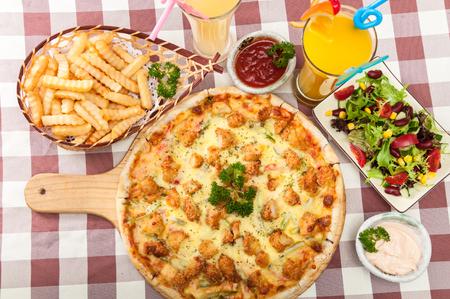 チキンのピザ、フライド ポテト、サラダ、ジュース