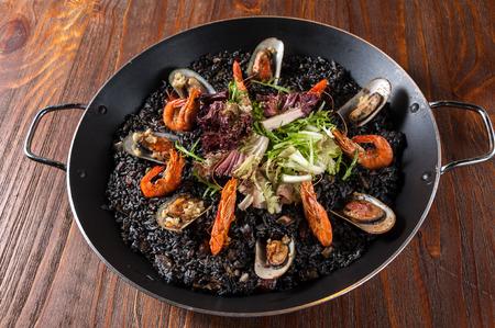 Paella, Meeresfrüchte mit schwarzem Reis Standard-Bild - 73884296