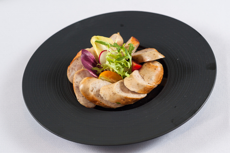 grilled sausage with vegetables in black dishes