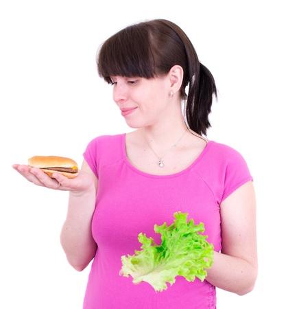 selects: The young woman selects between a hamburger and salad Archivio Fotografico
