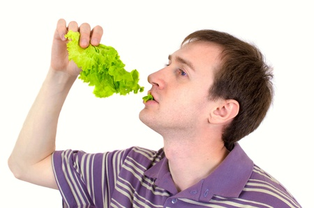 The young man is appetizing eats green salad photo