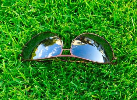 Sun glasses on a green grass photo