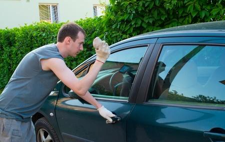 El hombre rompe una ventana del coche una piedra