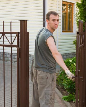 The man closes a gate photo