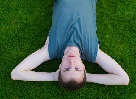 The young man lies on a green grass Stock Photo - 9730645