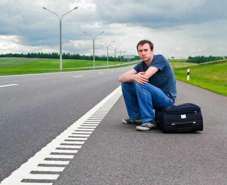 pending: The young man sits pending on road with a suitcase Stock Photo