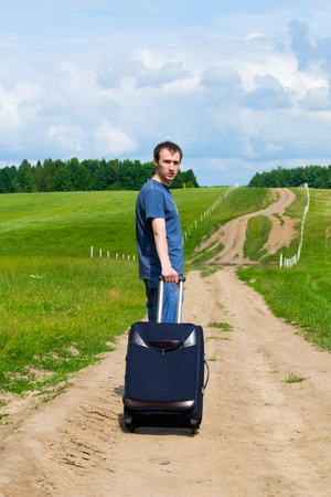 The young man on road in the field with a suitcase Stock Photo - 9954640