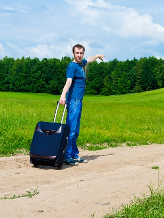 The young man on road in the field with a suitcase Stock Photo - 9954684