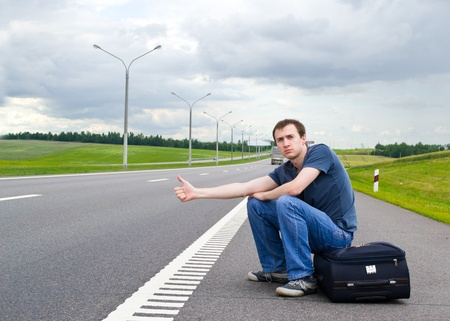The young man sits pending on road with a suitcase Stock Photo - 9954676