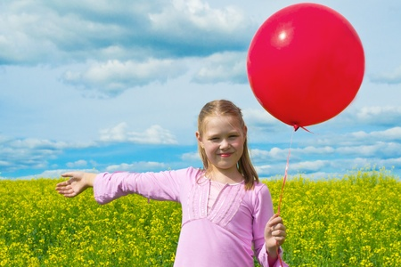 Girl with balloon in meadow photo