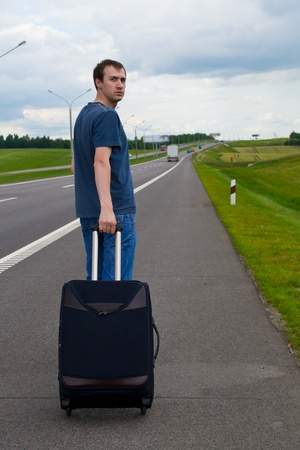 The young man pending on road with a suitcase Stock Photo - 9954729