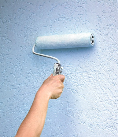 new construction renovation: Roller with paint on the wall Stock Photo