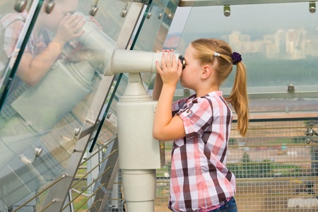 Young girl looking through tourist telescope , exploring landscape. photo