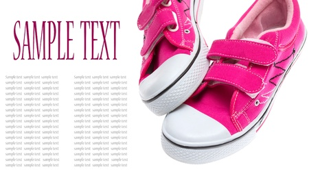 Pink sneakers isolated on white background with sample text  photo