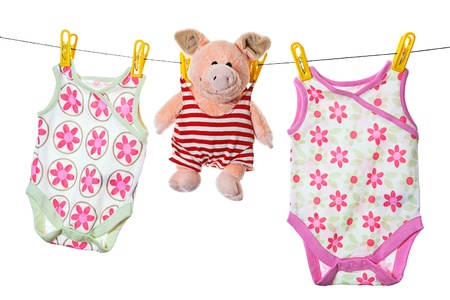 Baby sleepers and pig on the clothesline, studio isolated on white. photo