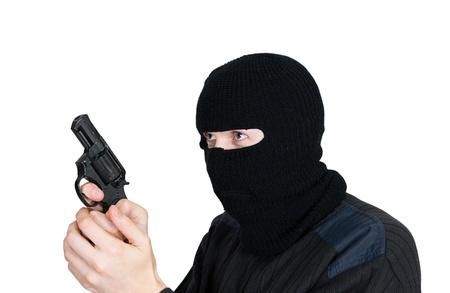 hijacker: hombre en una m�scara con un arma de fuego sobre un fondo blanco Foto de archivo