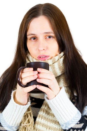 Young woman caught cold, wrapped up in blanket, drinking something hot from cup. Stock Photo