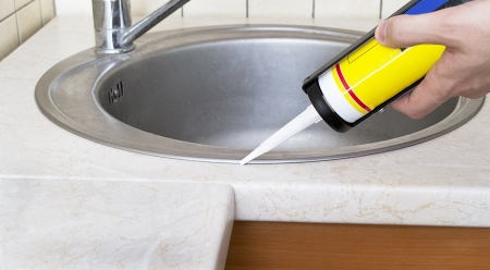 Plumber putting a silicone sealant to installing a kitchen sink Stock Photo - 12303129
