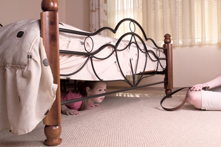 The child hides under a bed. Violence in a family. photo