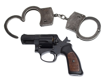 Handgun with handcuffs and bullets isolated on white photo