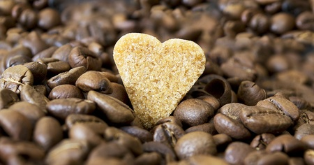 Pieces of sugar on the background of coffee beans. Stock Photo - 13549191