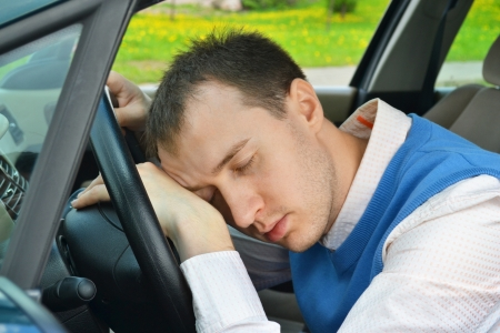 the weariness: Man sleeps in a car.