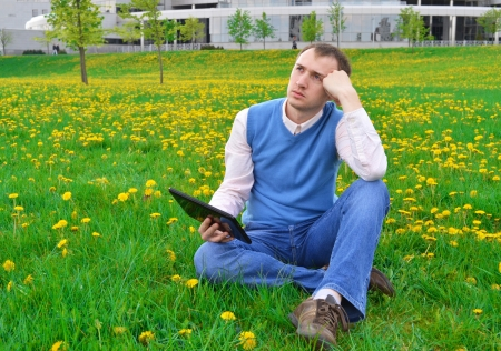 Businessman at the park with tablet. photo