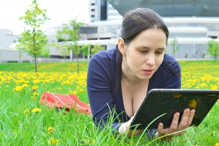 Young beauty student girl with tablet on nature background photo