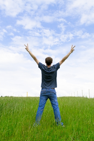 lifted hands: The young man on a meadow having lifted hands upwards