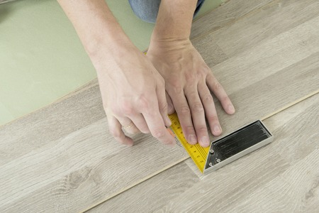 underlay: Man with Tools to Laying Laminate. Working time