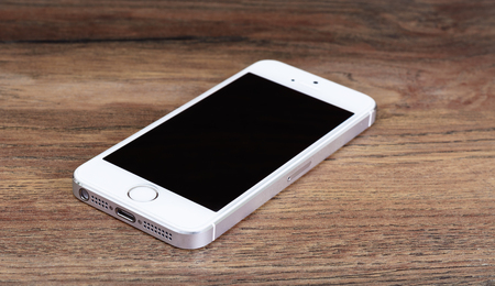 ios: Minsk, Belarus - April 16, 2016: Apple iPhone 5, 5S. White version. Front view. The operating system iOS 9. The founders of the company: Steve Jobs, Ronald Wayne, Steve Wozniak. Apple Inc. Located in USA.