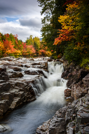 Swift river at rocky scenic gorge area during fall season Imagens