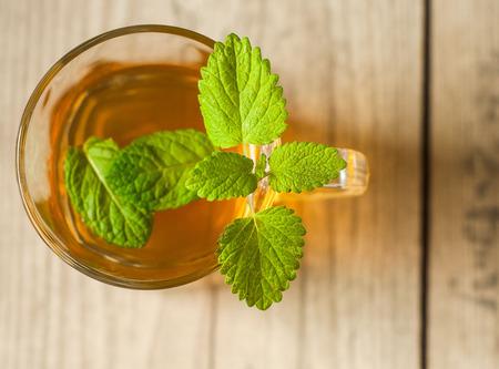 Tasse Tee mit Minze auf Holztisch