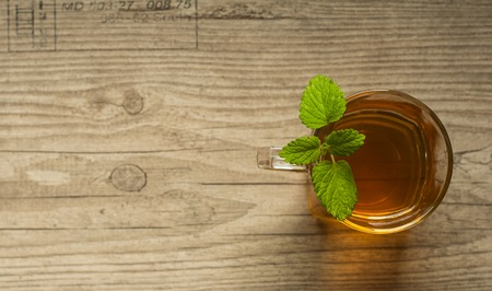 cup of tea with mint on wooden table photo