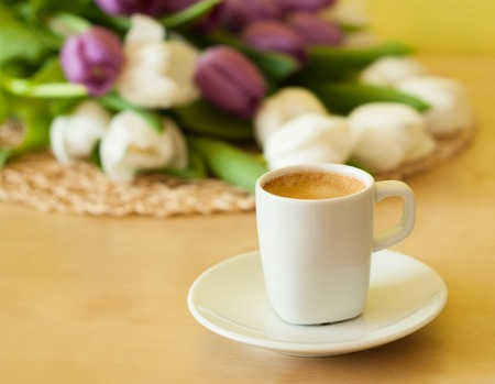 tulips on the table with cup of caffee photo