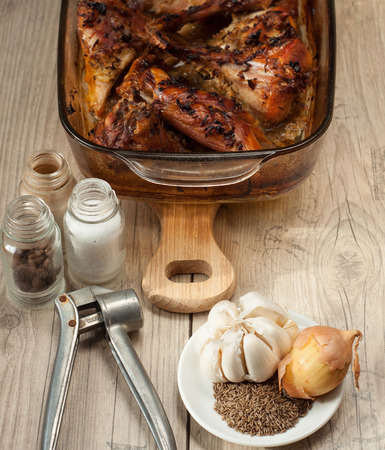 bunny xmas: rabbit meat roaster with onion cumin and garlic on wooden vintage table